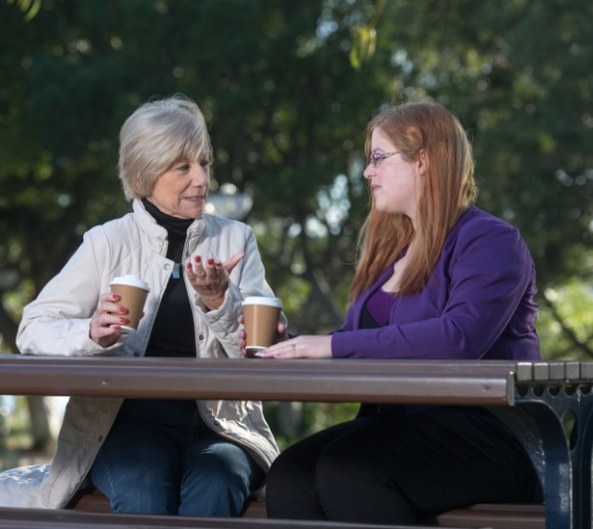 Senior woman talking with younger woman in park
