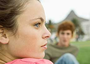 Teen aged girl and boy sitting outside on the grass